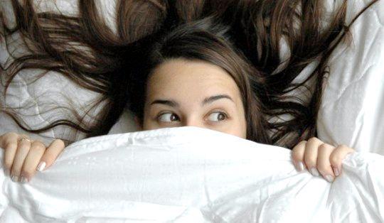 Дівчина ховається під ковдрою